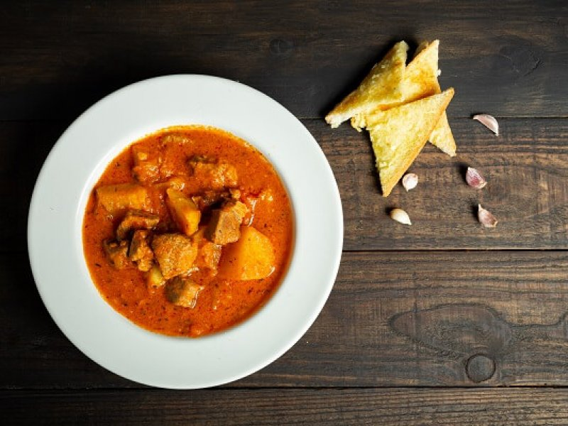 Goulash soup on wooden background.